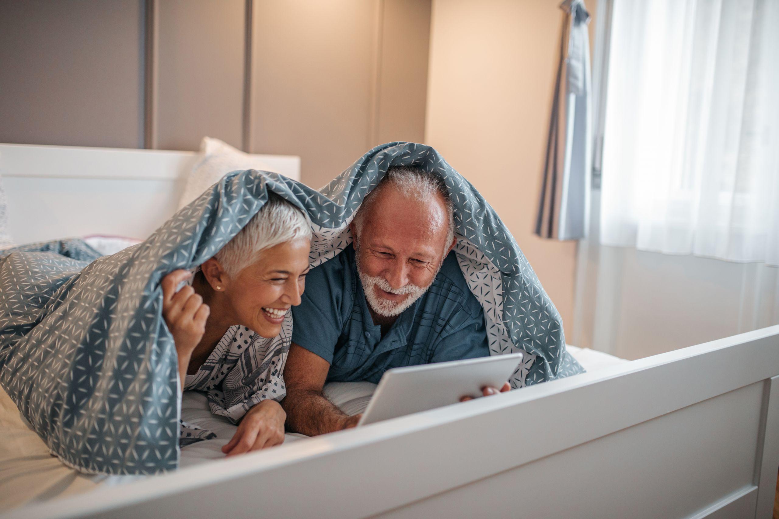 couple heureux de sénior au lit en train de lire une tablette et de s'informer
